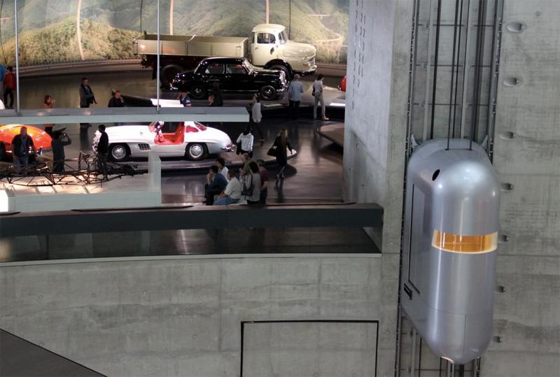 В музее легендарного автомобильного концерна Мерседес-Бенц в Штутгарте без темы автопрома не обошлось даже оформление лифтов. Подъемники стилизовали под футуристические капсулы, напоминающие линейку концепт-каров. Они бесшумно поднимают посетителей на 9-й этаж, с которого начинается экспозиция.