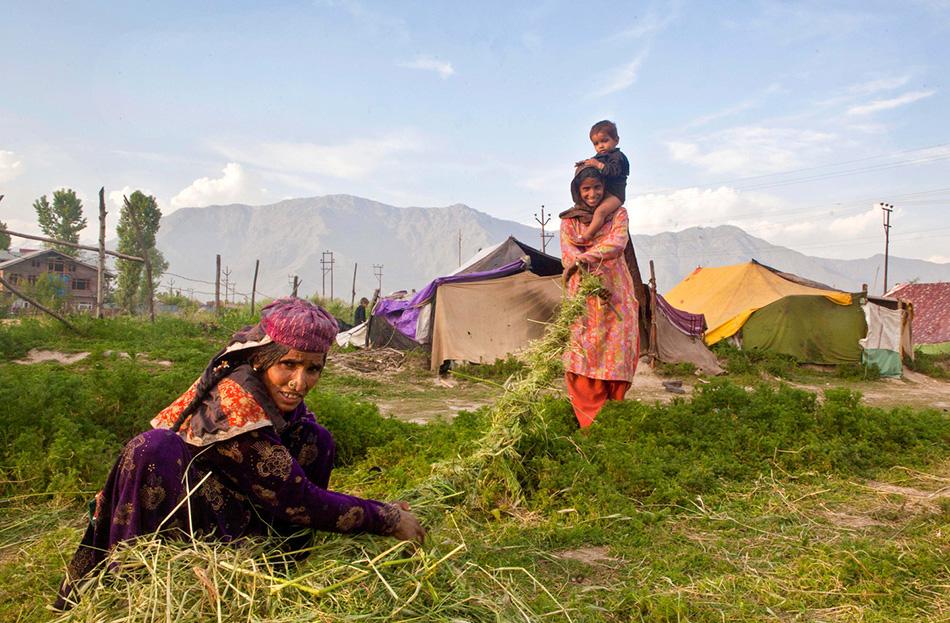 Женщины из кочевой общины вьют веревку из травы неподалеку от своего лагеря.