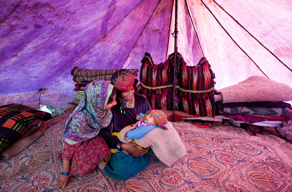 Женщина вместе с дочерью играют в палатке с ее сыном Мохаммедом Маруфом.