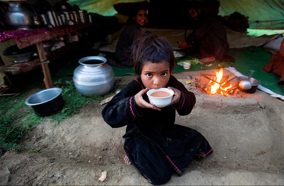 Девочка пьет чай, пока ее семья скоромится в лагере в предместьях Сринагара.