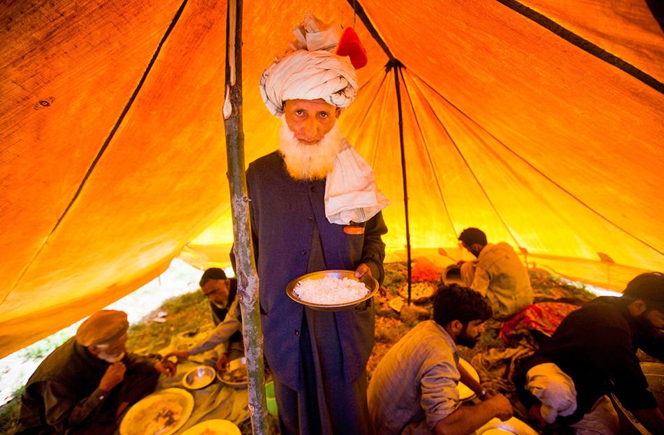 Абдул Рахим держит тарелку с рисом во время свадебной церемонии внутри большой палатки.
