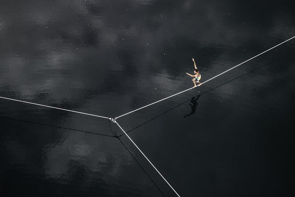 Канатоходец Джереми Тетаз во время выступления на озере близ швейцарского города Сьон.