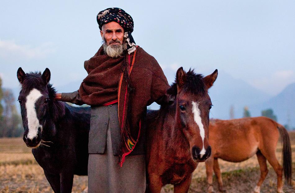 Шокат Хан позирует со своими лошадьми в лагере рядом со Сринагаром.