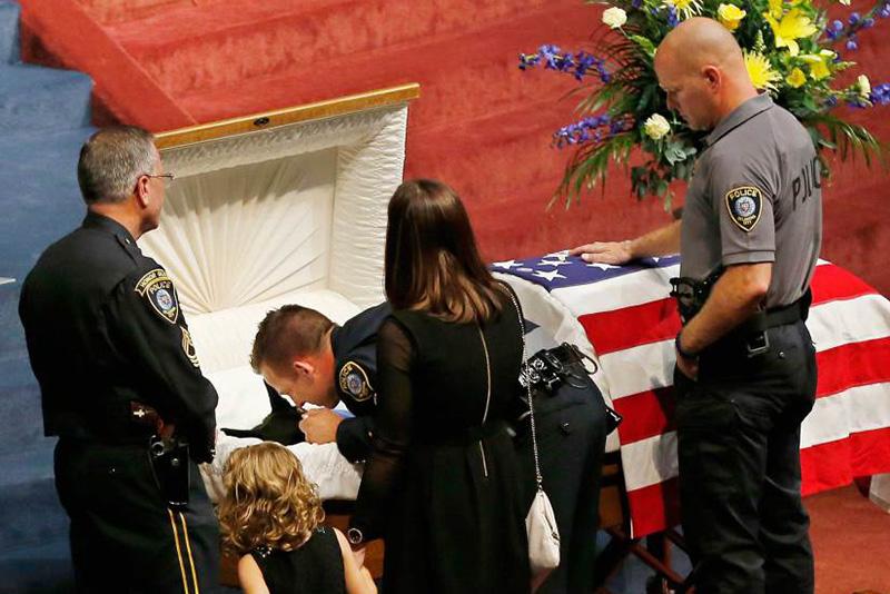 Сержант Райан Старк из полиции Оклахома Сити склонился над гробом своего четвероногого напарника по кличке Кай. 28 августа 2014.