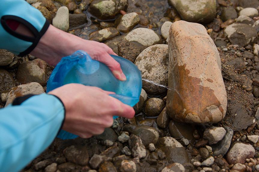 Устройство для промыванияран Налейте несколько кружек очищенной воды в пакет, после чего скрутите его так, чтобы вся вода собралась в одном углу. Проколите небольшую дырку, и вы сможете промыть рану тонкой струей воды.