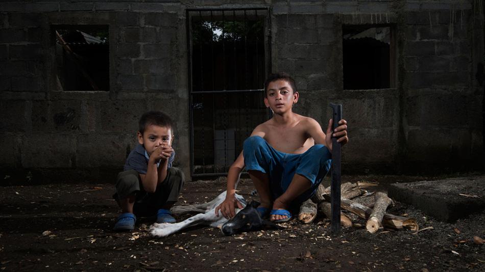 Мачете №45: Типитапа, Никарагуа Брайан начал пользоваться мачете в пять лет. Он зарабатывает по 80 центов за полдня, вычищая траву вокруг деревьев. На фото он со своей собакой Камиллой и младшим братом Джонатаном после того, как нарубил дров для своей семьи.