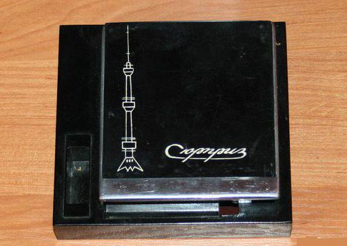 «Сюрприз» — нетипичная зажигалка, совмещающая в себе небольшой портсигар и пьезоэлемент вместо привычного кремня для воспламенения.