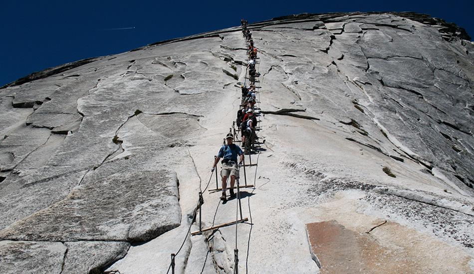 Канатная лестница на вершину Халф Дом, США Знаете, что лежит между вами и самым известной горной вершиной Национального парка Йосемити в Калифорнии? 10-километровый путь сквозь дикую местность с постоянно возрастающим уклоном, увенчанный подъемом более чем на 100 метров вверх прямо по поверхности горы по канатной лестнице. Пройтись по ней в день могут не более 300 человек, каждому из которых дается специальное разрешение.