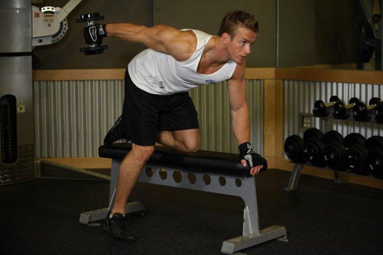Тяга гантели в наклоне Возьмите гантель в правую руку. Обопритесь коленом левой ноги на скамью. Немного наклонитесь вперед и упритесь левой рукой в край скамьи. Сделайте глубокий вдох и поднимите гантель вверх. Через пару секунд выдохните и плавно опустите. Все усилия предпринимайте, задействуя только мышцы спины и плеч.