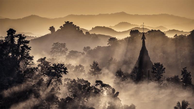 Вид с вершины горы в городе Мраук-У. Со всех сторон панорама с холма в древнем городе в штате Ракхайн на западе Мьянмы была окутана туманом и дымом. Это священное, уединенное место без толп туристов.