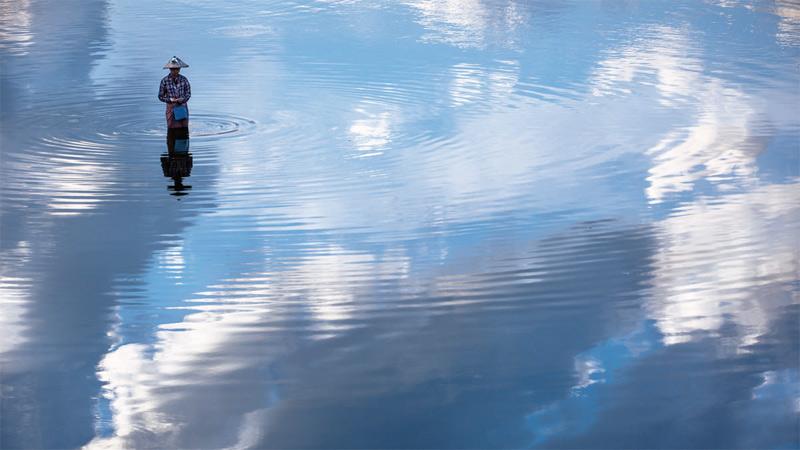 Женщина во время рыбалки. Однажды утром, прогуливаясь по знаменитому мосту У-Бэйн, построенному в 1849 году из тикового дерева, Дэвид заметил внизу женщину, которая ловила рыбу. В озере отражались облака, создавая иллюзию, что женщина ходит по небу.