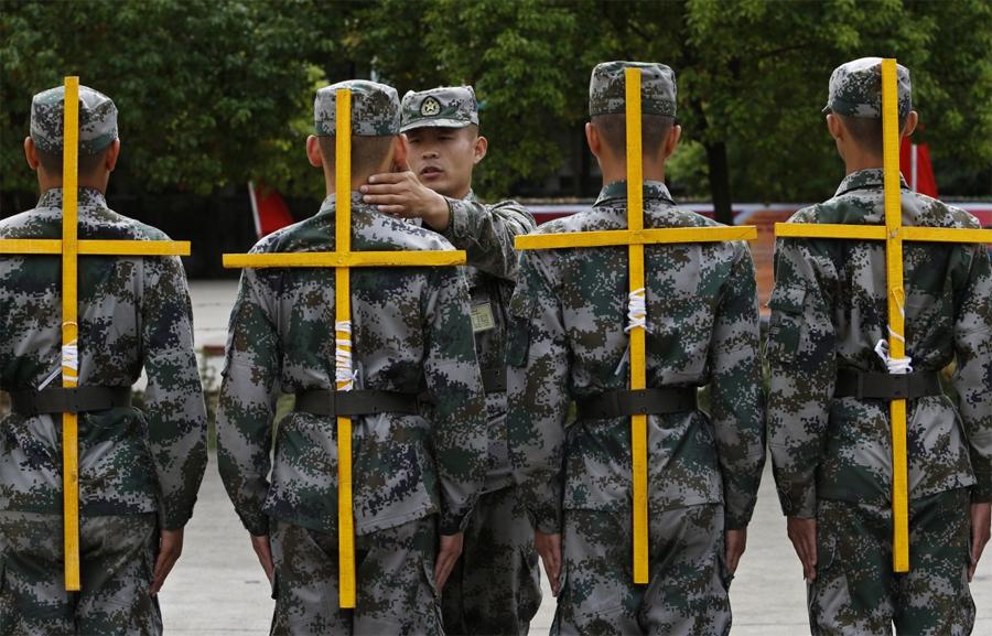 Маршировка с крестом за спиной Локация: Ханчжоу, КитайГод: 2013 Маршировка с крестом, примотанным к твоей спине, является частью маршевых занятий в Китайской освободительной армии. По словам китайских инструкторов, она не только вырабатывает правильную осанку у солдат, но и дисциплинирует их.