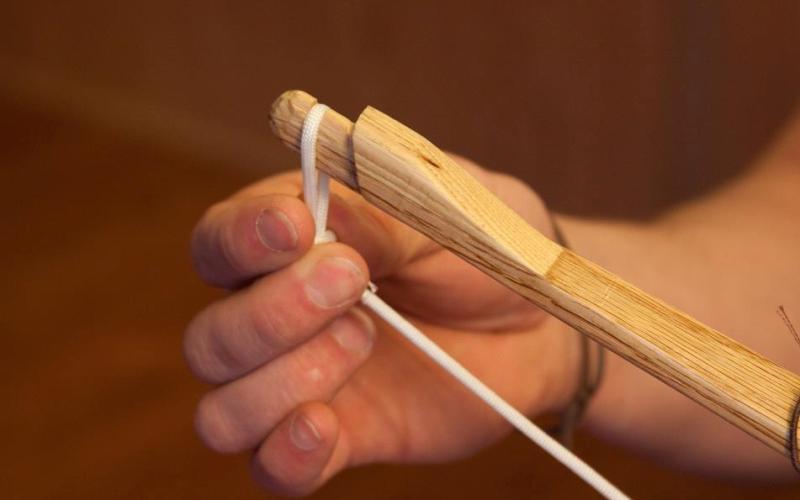 Закрепить тетиву Тетива по размерам должна быть несколько короче лука, так, чтобы и она и лук находились все время в слегка натянутом состоянии. Закрепив тетиву в одной засечке, при мощи узелка привяжите в этом месте тетиву к луку. Протяните свою тетиву к оставшейся зарубке и завяжите еще один узелок.