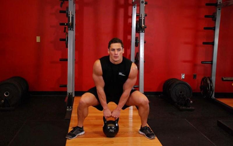 Становая тяга Становая тяга – это замечательное упражнение, которое нагружает различные мышцы ног, тазового пояса и спины. Широко расставьте ноги, спина прямая, выполните приседание. Возьмите гирю двумя руками и, не округляя спину, встаньте. Старайтесь подняться, используя сил мышц бедер, а не вытягивая гирю руками.
