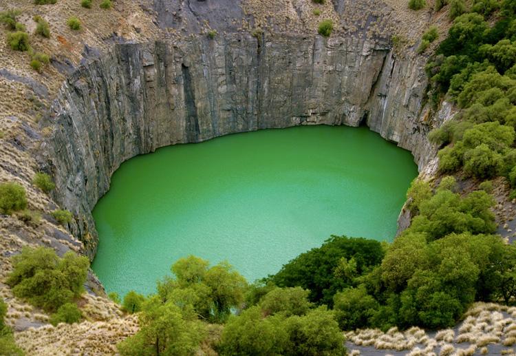 Большая дыра, ЮАР Карьер был выкопан в период с 1866 по 1914 год с помощью кирок и лопат. За это время здесь добыли 2722 кг. алмазов и извлекли на поверхность примерно 22,5 млн. тонн грунта. Площадь карьера составляет 17 гектаров. Его периметр достигает 1,6 км, а ширина — 463 метра. Изначально глубина дыры составляла 240 метров, но позднее она была засыпана пустой породой до глубины 215 метров. В настоящее время дно затоплено водой.