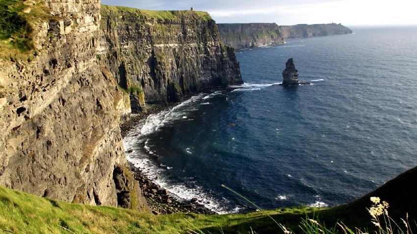 Западное побережье Ирландии Одной из визитных карточек Ирландии считается западное побережье графства Клер. В этом месте расположены самобытные домики, древние развалины и знаменитые на весь мир утесы Мохер, протяженностью 8 км. и высотой 200 метров. Чтобы рассмотреть все это великолепие,лучше всего арендовать машину и отправиться по узким проселочным дорогам к живописному берегу Атлантического океана.