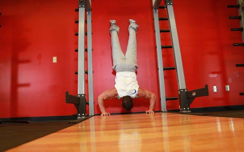 Отжимания в стойке на руках Этот вид отжиманий одно из самых эффективных упражнений с собственным весом. Мышцы от него растут быстрее, чем можно было ожидать. Для планомерного развития мышечной силы вам придется выполнять отжимания с опорой на стену. Ставьте руки на ширине плеч, когда закидываете ноги на стену, не слишком близко к стене (15-17 см). Стены должны касаться только пятки, вес всего остального вашего тела держите сами.