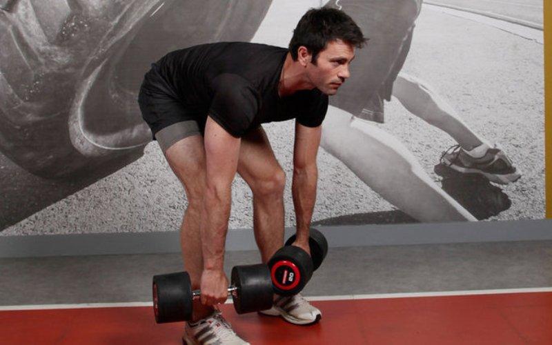 Румынский подъем Этот вид становой тяги призван увеличить силу мышц ягодиц и бедер. Ноги на ширине плеч, колени слегка согнуты. Возьмите в руки гантели и плавно, на прямых ногах, нагнитесь вперед, удерживая спину прямой. Доведите гантели до середины голеней и на выдохе вернитесь в исходное положение. Делайте вдох при наклоне и выдох, когда поднимаете гантели.