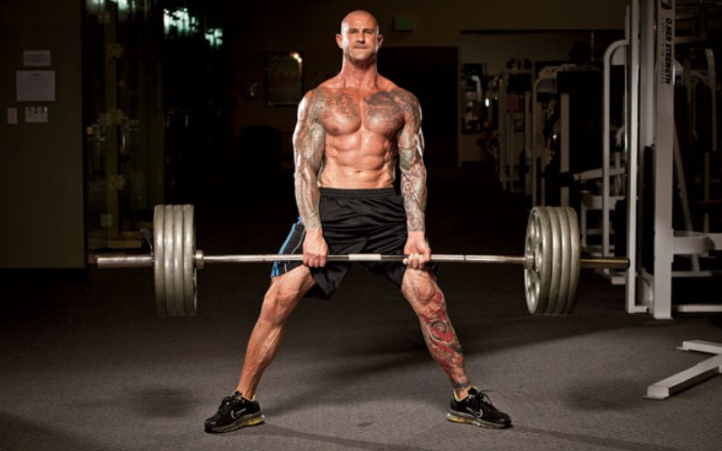 Становая тяга Наверное, нет более полезного упражнения, которое задействовало бы такое большое количество мышечных групп и развивало их так быстро. Многие тренеры не рекомендует выполнять его, так как неправильное выполнение ведет к травматизму. Ноги поставьте чуть уже ширины плеч и беритесь за гриф. Оставляя спину ровной, поднимаем штангу так, чтобы гриф двигался как можно ближе к ногам. Основная нагрузка приходится на ноги. Достигнув верхней точки, задержитесь на 1-2 секунды и медленно опустите штангу.