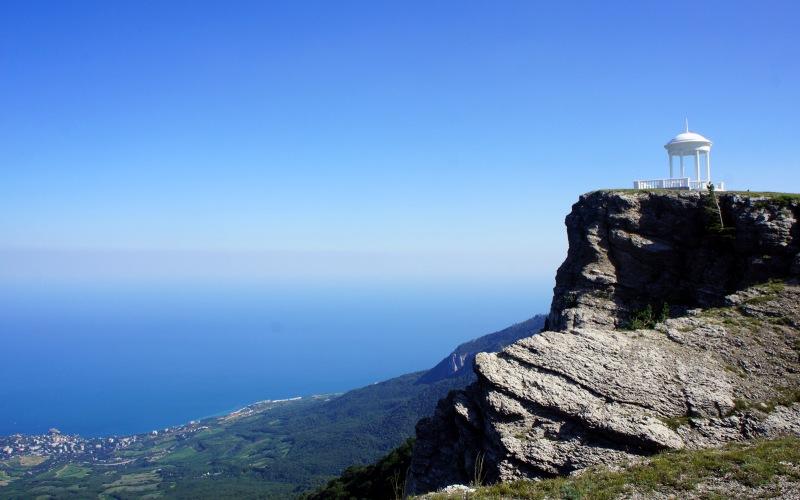 Беседка ветров На вершине Шаган-Кая на высоте 1450 метров расположена каменная беседка, построенная в 1956 году. Мозаика на ее полу изображает розу ветров, благодаря которой беседка и получило свое название. Отсюда открывается изумительный вид на гору Аю-Даг, Гурзуф, Партенит и Черное море, которое в ясную погоду просматривается на 150 километров. Рядом с беседкой находится пещера, в которой даже в самую жаркую погоду царит зима и лежит снег.