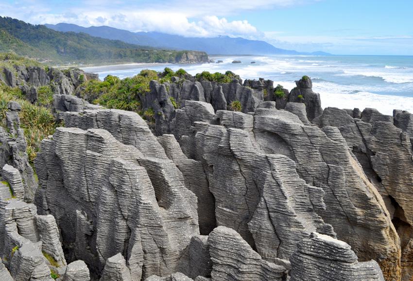 Блинные скалы, Новая Зеландия Скалы расположены на западном побережье Новой Зеландии. Сформировались они несколько миллионов лет назад, в период когда вместо суши здесь было море. После того как образования поднялись с морских глубин, ветер и вода доработали ландшафты, создав бороздки, благодаря которым скалы напоминают стопки блинов.