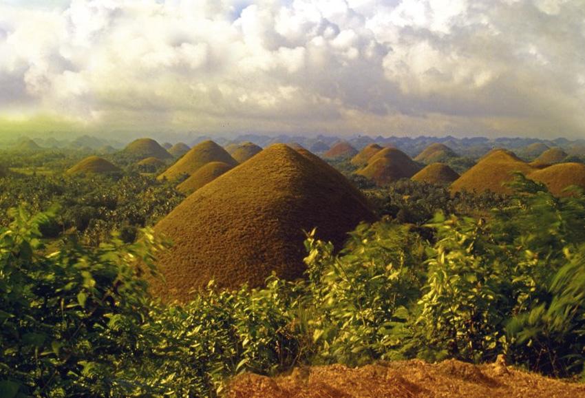 Шоколадные холмы, Филиппины Почти симметричные возвышения занимают почти 50 кв.км. в провинции Бохоль. По разным данным, здесь насчитывается от 1200 до 1800 холмов. Большую часть года они покрыты травой, но во время сухого сезона она приобретает коричневый цвет, из-за чего пейзаж выглядит абсолютно инопланетным.