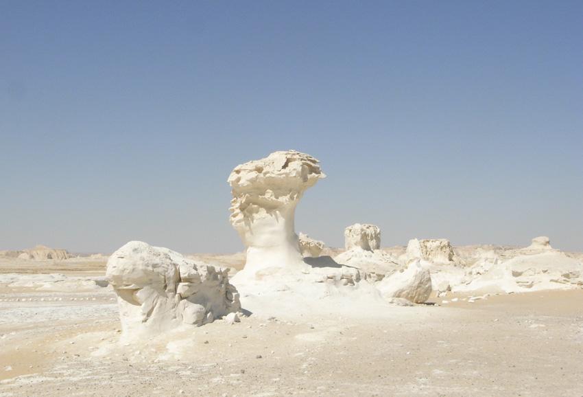 Белая пустыня, Египет На востоке пустыни Сахара располагается небольшой, уникальный участок, 365 дней в году выглядящий так, будто его буквально несколько минут назад засыпало снегом. Несколько миллионов лет назад здесь располагалось дно океана. Отступив, вода оставила на суше известняковые отложения, сформировавшиеся из останков морских микроорганизмов. Некоторым из них со временем ветер придал форму скульптур.