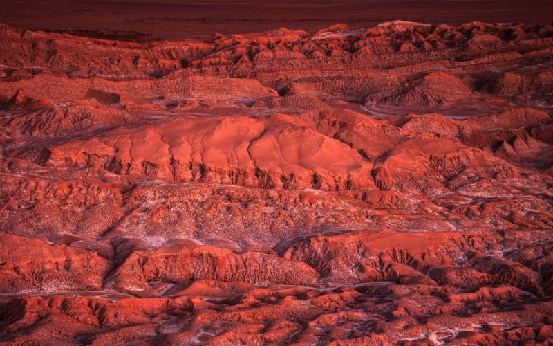 Из Сантьяго в Калама Протяженность перелета: 4665 км / 7 часов Самолет рейсом Сантьяго-Калама долгое время летит над вершинами заснеженных Анд. Спустя примерно две третьих маршрута, зубчатые горы внезапно переходят в пустыню – на этом месте когда-то было соленое озеро. На закате эта область возле Каламы в Чили выглядит как лишенная жизни поверхность Марса.