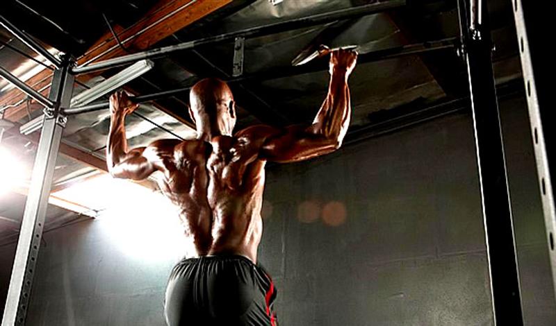 Широкий хват Подходы: 3Повторения: 10-12Отдых между подходами: 45 секунд Для этого упражнения, вам потребуется только турник и сила воли — чтобы до него добраться. Возьмитесь за перекладину широким хватом, так, чтобы руки стояли шире плеч. Плавно поднимайте тело вверх, начиная движение усилием спины, а не рук. Старайтесь подниматься так высоко, чтобы коснуться перекладины верхней частью груди. Если не получается — лучше снизить количество повторов, но выполнять их правильно. Не делая остановок, также плавно опускайтесь вниз и повторяйте до победного.