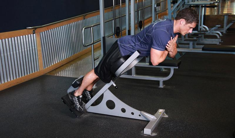 Гиперэкстензия Подходы: 4Повторения: 15Отдых между подходами: 30 секунд Это упражнение, помимо прочего, подарит занимающемуся хорошую осанку, так как направлено на развитие длинной мышцы спины. Устраивайтесь на скамье для гиперэкстензии поудобнее (впрочем, подойдет и высокая кровать, лишь бы ноги были закреплены). Ноги выпрямлены, руки скрещены на груди. Опускайтесь вниз, до конца и, без задержки, поднимайтесь в исходное положение. Торопиться не стоит, вы тут, в конце концов, делом занимаетесь.