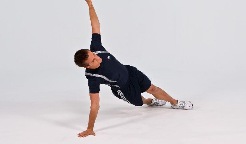 Т-образные отжимания Развивают: грудные мышцы, трицепс, дельтовидные мышцыКоличество подходов: 3Количество повторов: 8 на каждую рукуОтдых между повторами: 45 секунд Итак, примите исходное положение, как при обычных отжиманиях. Выполнив подъем, оторвите и поднимите левую руку вверх. Задержитесь на несколько секунд, плавно вернитесь в упор лежа и повторите упражнение, подняв, на этот раз, правую руку. Для усиления эффекта используйте гантели. Запомните: локти не должны торчать в стороны, а мышцы кора лучше напрягать все время повторов. Не стоит делать слишком сильный, рывковый поворот руки.
