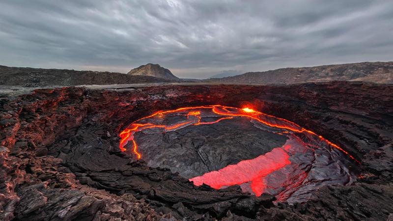 Эрта Але Эфиопия Это самое неподходящее для существования человека место на нашей планете. Когда садится солнце, дым начинает выходить из трещин под вашими ногами, а жуткое, кроваво-красное свечение исходит из лавовых озер, которых здесь насчитывается целых пять штук. Температура воздуха достигает 55 градусов по Цельсию: отправиться сюда может отважиться лишь самый храбрый путешественник.