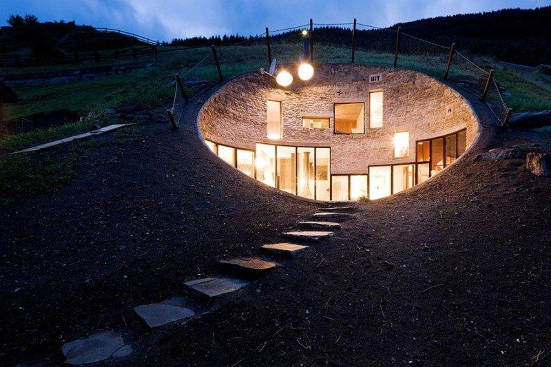 Дом внутри горы в Альпах Шесть лет назад архитекторы из агентств SeARCH и CMA объединили усилия, чтобы создать особняк, расположенный прямо внутри горы в швейцарских Альпах. Несмотря на этот, мягко говоря, необычный архитектурный прием, дом по степени комфорта легко обгонит даже уютную хоббичью нору. В гостевом доме, сдающемся, кстати говоря, в аренду, всегда много света, благодаря стеклянному фасаду и большому количеству окон, и свободно может разместиться до десяти жильцов.
