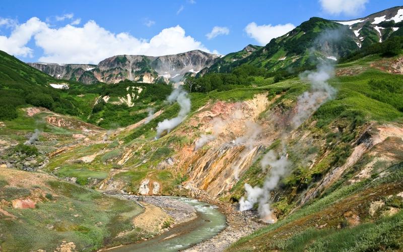 Долина Гейзеров Этот крохотный участок земли, напичканный чудесами, глубоко запрятан в горных урочищах Камчатки. Долина Гейзеров прячется в труднодоступном ущелье на территории Кроноцкого биосферного заповедника, и добраться сюда можно только на вертолете. В 1934 году сотрудником новообразовавшегося заповедника, Татьяной Устиновой, исследовавшей ущелье, было обнаружено здесь более 20 крупных гейзеров, не считая сотни красочных термальных источников, кипящих ключей и горячих озер. Абсолютно фантастический ландшафт дополняет изумрудно-зеленая буйная зелень, рисуя сказочную, как будто явившуюся во сне, картину.