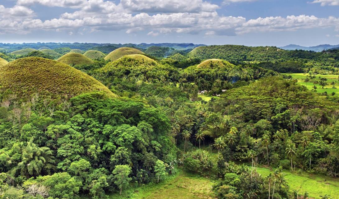Эти горы необычной формы — знаменитые Шоколадные холмы. До сих пор никто из геологов не смог в точности доказать причины их возникновения.