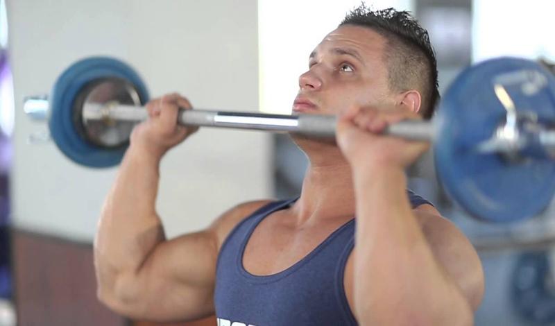Жим штанги стоя Это упражнение считается одним из самых эффективных для развития мышц плечевого пояса. Вместе со становой тягой и жимом от груди, жим штанги вверх формирует пул обязательных базовых упражнений, пропускать которые не рекомендуется никому. Помимо значительного роста мышц, вы разгоните и метаболизм. Итак, возьмите штангу обычным хватом: руки на ширине плеч, поднимите ее до подбородка. Поднимайте штангу до полного распрямления локтей. В пике — небольшая пауза, и повтор.