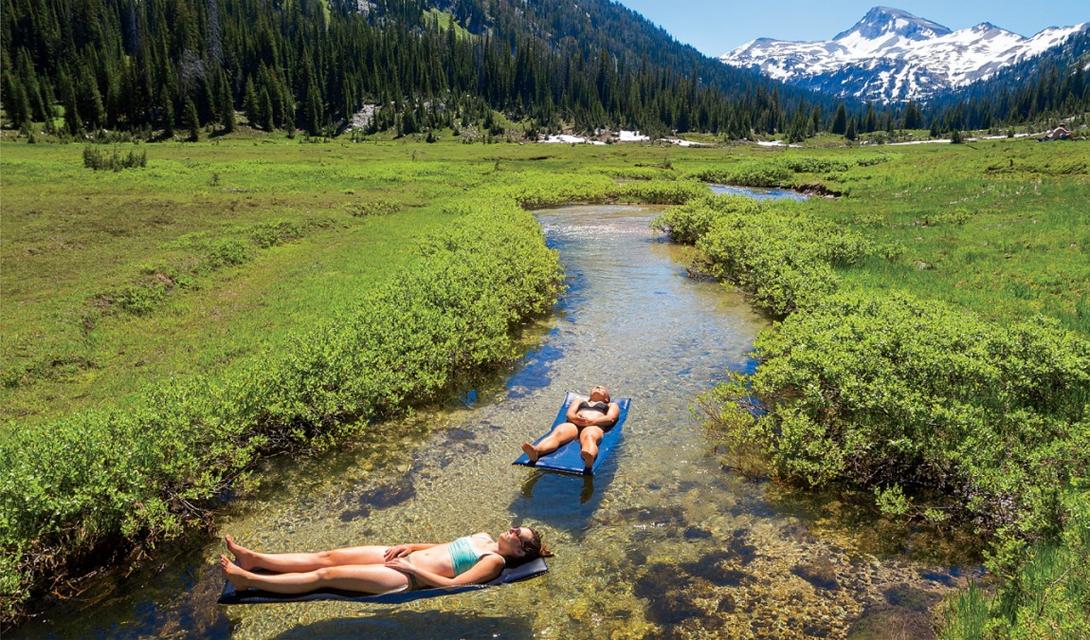 Валуа-Уитмен Две женщины наслаждаются полуденным солнцем на реке национального парка Валуа-Уитмен, Орегон.