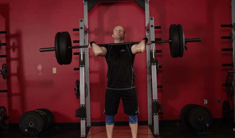 Жим штанги стоя Еще одно базовое упражнение, выполнение которого очень быстро приведет вас в нужную форму. Жим стоя прорабатывает, в основном, средний пучок, но два других тоже задействованы. Поставьте ноги на ширине плеч, штанга на уровне груди, прямой хват. Поднимайте штангу вверх, делая выдох на пике. Сделайте три подхода по двенадцать повторов в каждом.