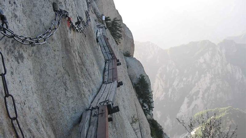 Китай, Хуаинь,гора Хуашань Паломничество На вершине горы на высоте 2000 метров располагается старинный храм. Добраться до него можно по канатной дороге или оборудованным лестницам, но самые отчаянные не ищут легких путей и выбирают для подъема узенькую тропинку из досок шириной около 50 сантиметров. Для страховки путешественников пристегивают тросами к закрепленным в скале цепям.