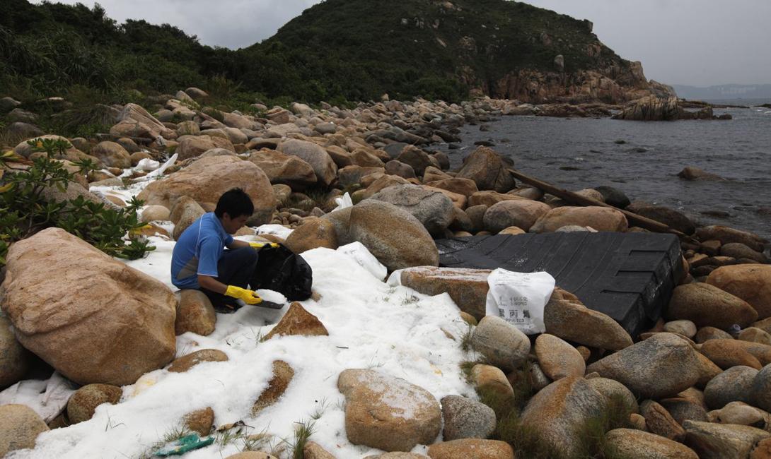 Волонтер убирает пластиковые гранулы на берегу. Сотни миллионов таких гранул оказались в море после тайфуна, перевернувшего гигантский контейнеровоз.