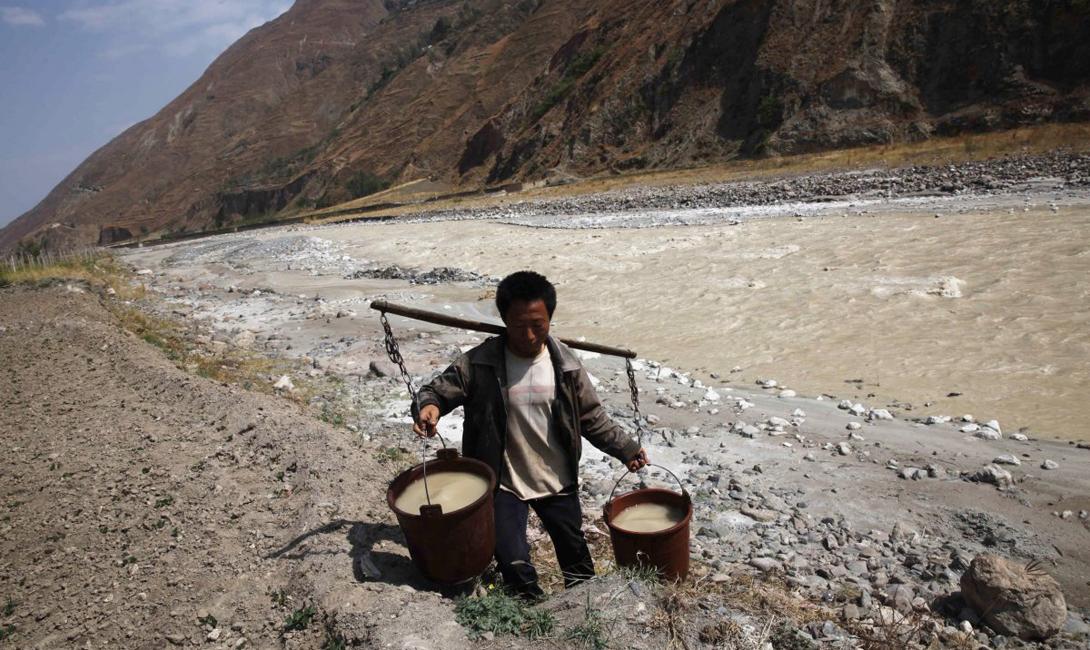 Сельский житель несет ведра питьевой воды из загрязненной реки. Китай, провинция Юньнань.
