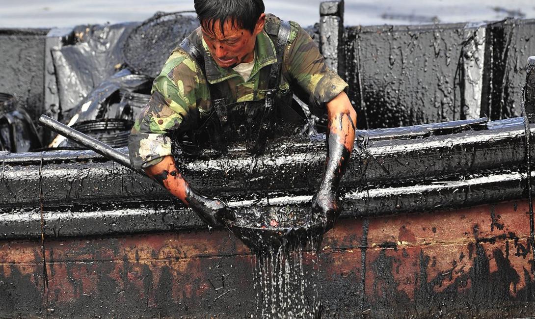 Рабочий черпает масло рядом с портом Далянь в провинции Ляонин, Китай. Девять дней спустя после того, как лопнул трубопровод, образовалась утечка и 1500 тонн тяжелой нефти попали в воду.