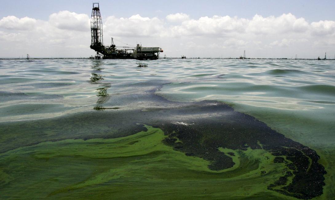 Нефть плавает на воде вблизи производственного объекта в Маракайбо.