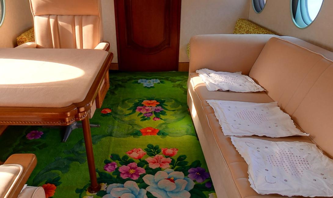 Обстановка внутри напоминает пасторальную картинку, нарисованную американской домохозяйкой со своего собственного жилища. Выбивается только ядовито-зеленый ковер — вполне в духе Северной Кореи.