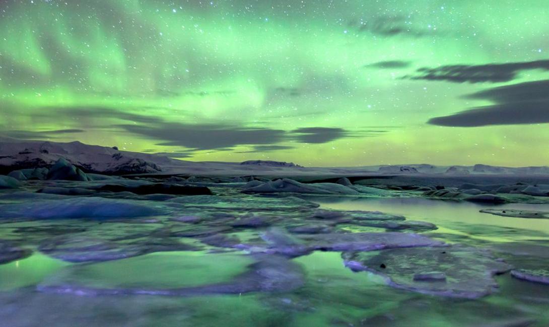 Йокюльсадлон Исландия Ледник у озера Йокюльсадлон и находящийся неподалеку замороженный пляж по праву считаются одними из главных чудес страны. Черный вулканический песок противопоставлен ледяным глыбам, белой каймой охватывающим весь берег. И, просто затем, чтобы вечер перестал быть томным — все это отражает раскинувшееся в небе северное сияние.