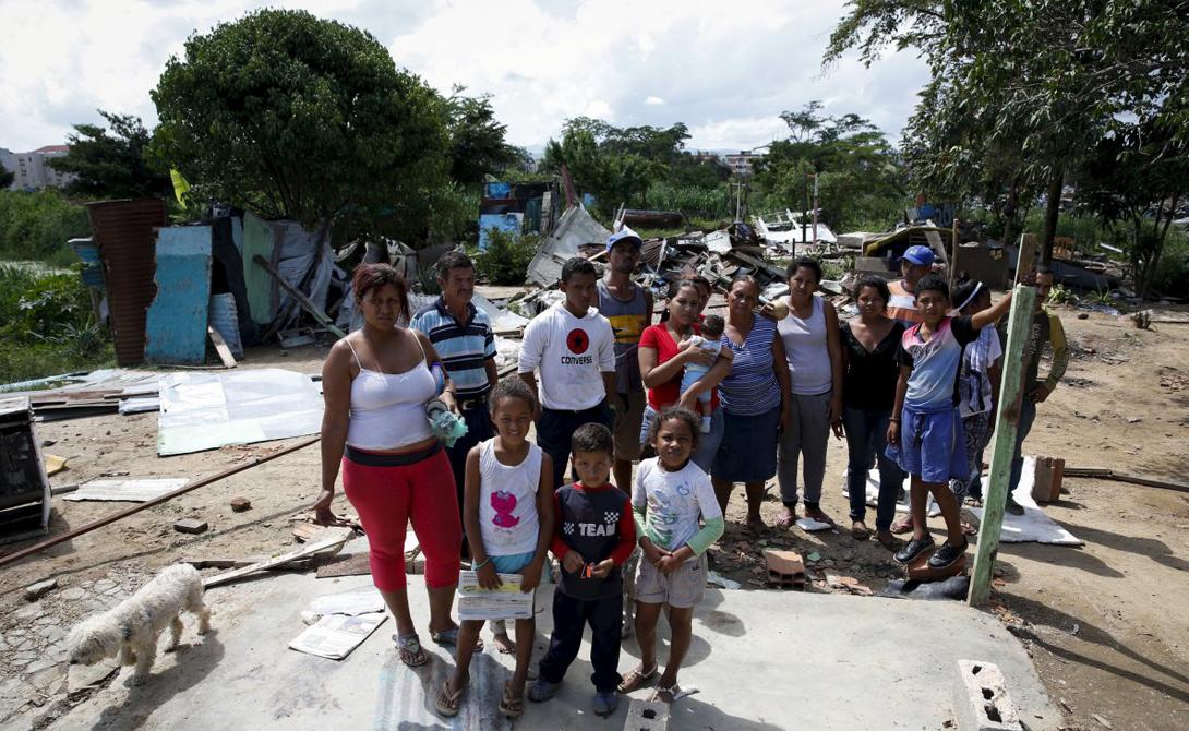 Валенсия Венесуэла Статистика: 72.31 убийств на 100 000 жителей Непонятно, кто наносит городу больше вреда — преступные группировки или служители закона, готовые пойти на все ради выполнения приказа. Эта семья позирует на фоне руин собственного дома, разрушенного правительственными чиновниками во время рейда под кодовым названием «Операция по освобождению людей».