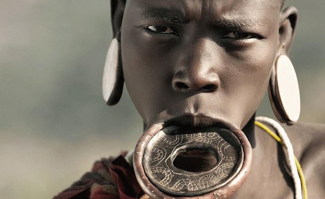 Мурси Африка Для девушек из африканского племени Мурси детство заканчивается примерно в 16 лет. После обряда инициации, шаман разрезает нижнюю губу несчастной и вставляет в отверстие небольшую палочку. Спустя какое-то время девушка начинает носить в губе небольшой каменный диск, постепенно расширяя отверстие. Особо влюбленные в современные тренды дамы мурси умудряются носить в губе настоящие блюда, пятнадцати сантиметров в диаметре. Нижние зубы при этом необходимо удалить, с ними украшение просто не помещается во рту.