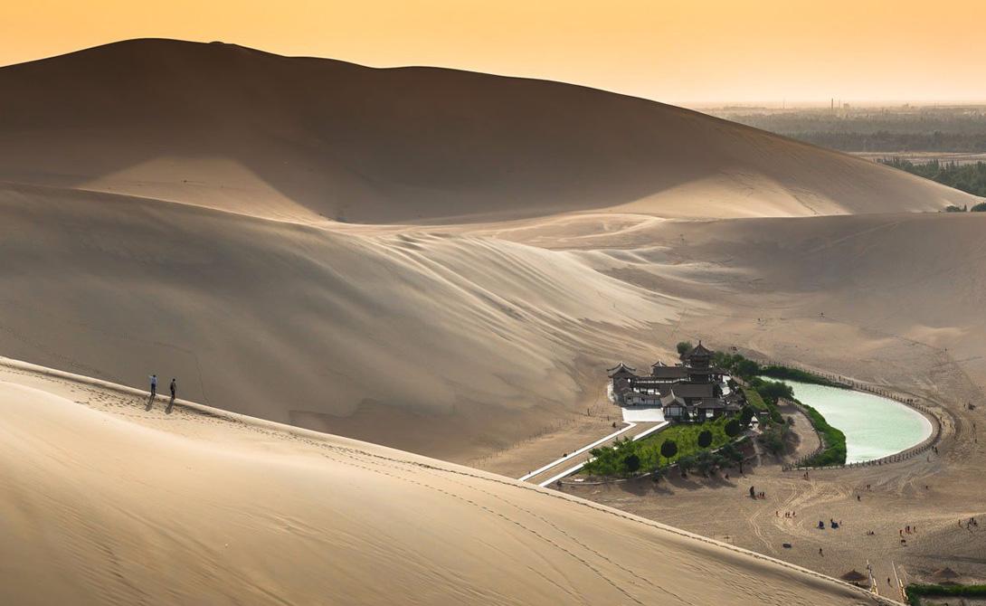 Оазис, как полагают, существует уже около 2000 лет. Здесь развлекаются катанием на верблюдах и серфингом на дюнах.