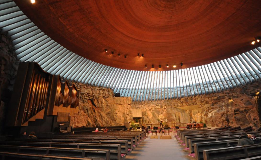 Вырезанная прямо в скале церковь Темппелиаукио, Хельсинки, получает достаточно солнечного света через застекленные купола. Эти грубые каменные стены были оставлены нетронутыми: дизайнеры справедливо решили, что естественная акустика сделает пространство храма идеальным для проведения религиозных служб и концертов классической музыки.