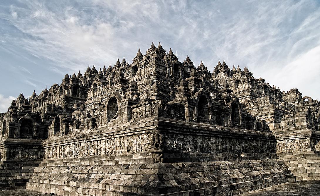 Храм Боробудур Индонезия Весьма примечательный архитектурный комплекс занимает всю вершину довольно высокого холма: храм Боробудур отличается необычной ступенчатой структурой невероятно искусной росписью по камню — ею покрыты многие стены и ступени постройки.